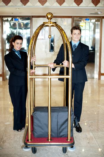 Concierge colleagues holding baggage cart
