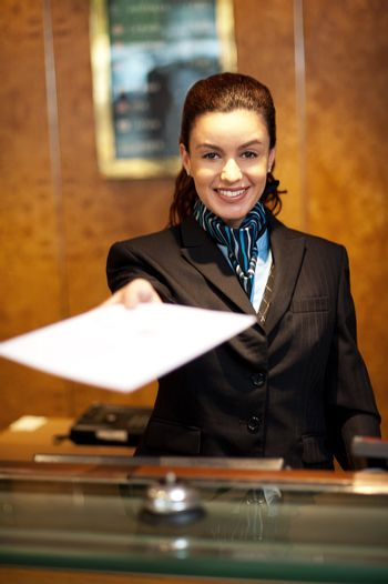 Cheerful female receptionist offering check-in papers