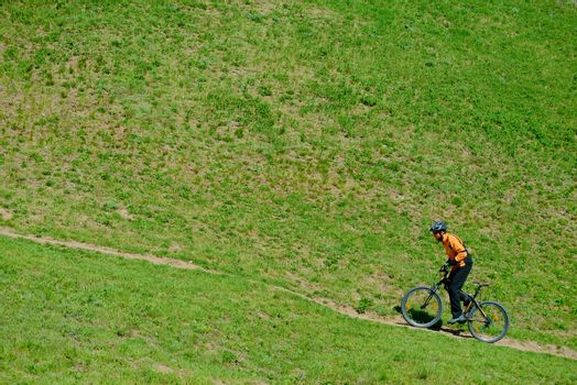 Cyclist Riding Up the Green Hill