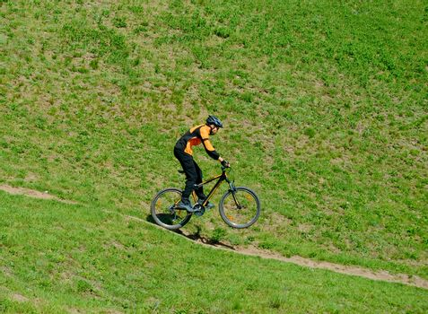 Cyclist Riding Down Hill on the Rear Wheel