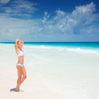 Cute female suntanning on seashore