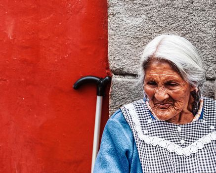 MEXICO CITY, MEXICO - JULY 14: portrait of unidentified old Mexican lady, sits next to traditionally colorfully painted house walls on July 14, 2012 on main street market in Mexico City, Mexico