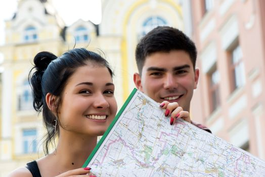 Young couple in town with touristic map