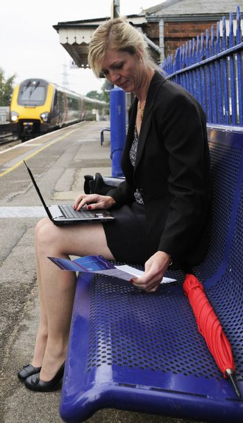 Businesswoman using a netbook computer Working on a railway station