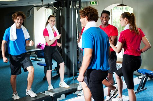 Couple with personal fitness trainer in the gym