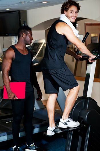 Young guy with his personal trainer beside him