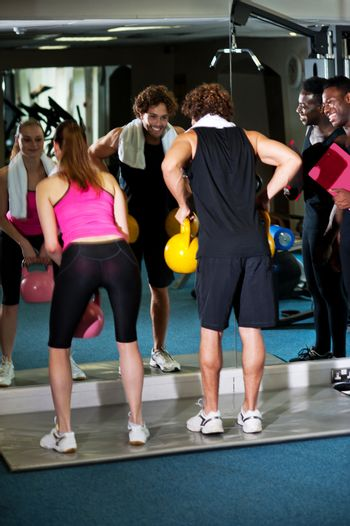 Male instructor keeping an eye on active gym members