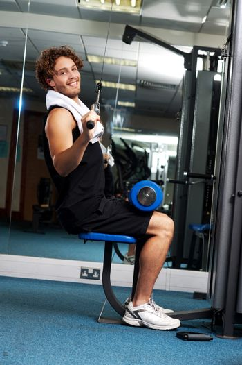 Man exercising with help of a hydraulic equipment