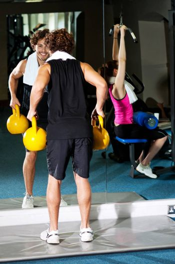 Athletic people working out with equipments