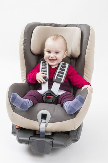 laughing child in booster seat for a car in light background.