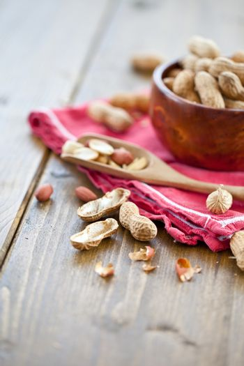 A wooden bowl filled with peanuts