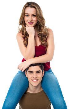 Pretty girl sitting on the shoulders of her boyfriend