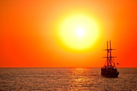 Tall ship drifting in the open sea at sunset.