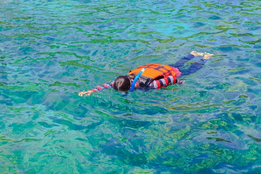 Asian girl snorkeling in a sea in Thailand