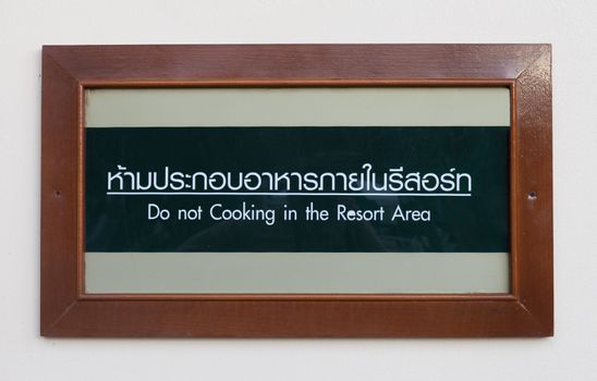 Wooden announcement frame on wall, saying Do Not Cooking in the