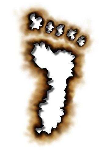 Carbon footprint or conservation symbol with  damaged burnt paper edges in the shape of a foot print as an icon of global warming with nature and the environment stopping pollution due to burning on a white background.