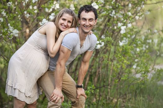 Young pregnant couple outdoors in spring blossom
