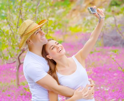 Cute cheerful couple make photo of themself outdoors on beautiful pink floral meadow in summer garden, affection and romance concept, happy weekend