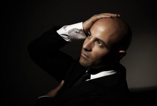 Bald man wearing black suit