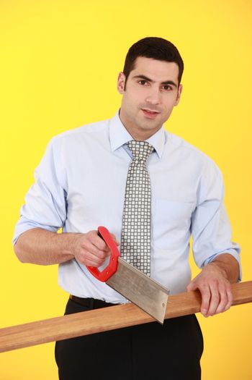 Businessman sawing wood