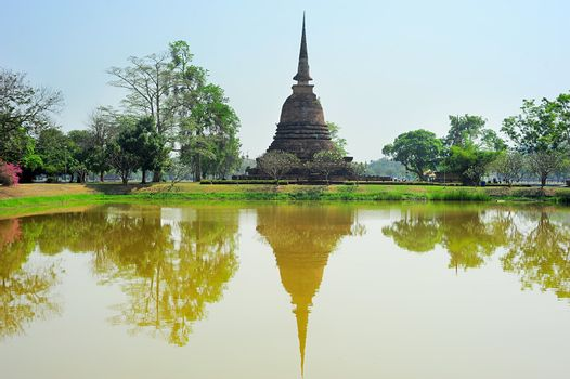 Pagoda reflected in the pond at  Sukhothai Historical Park . Thailand