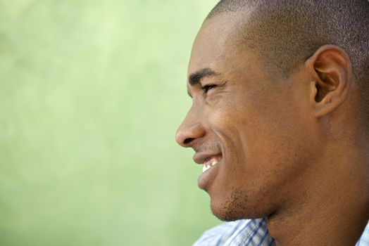 Portrait of happy young african american man looking away and smiling. Head and shoulders, copy space