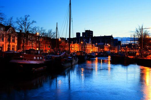 frozen canal with ships in Groningen in dusk