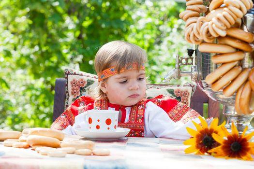 Girl in Russian national dress drinks tea from a samovar