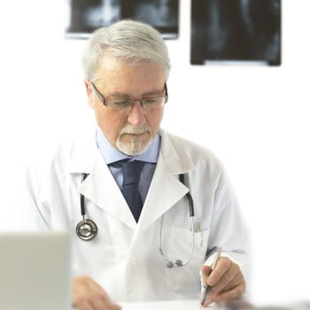 Doctor writing a prescription, on white background with x-ra