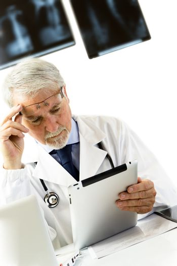 Doctor in clinic sitting at desk looking at x-rays on tablet