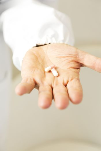 Doctor holding pills against anxiety