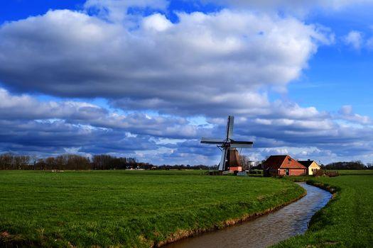 sunny day on Dutch farmland with windmill