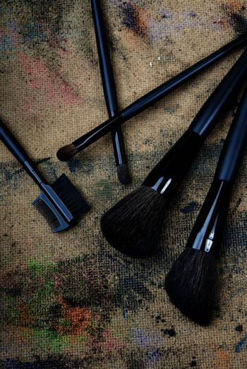 Close-up photo of five brushes on a dingy background