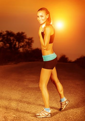 Woman doing exercise at sunset