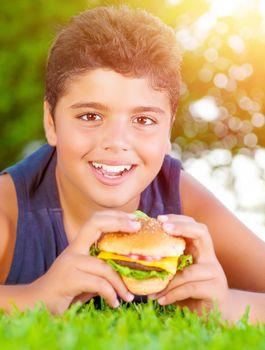 Arabic boy eating burger outdoors