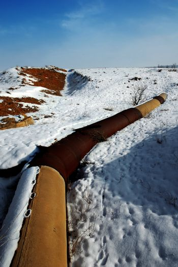 Rusted gas and oil pipeline under the snow