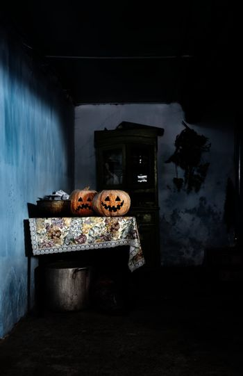 Two Halloween pumpkins in rural house with dark interior