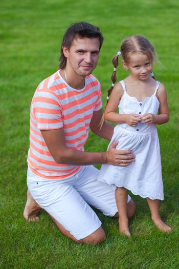 Portrait of father with his daughter sitting in the yard
