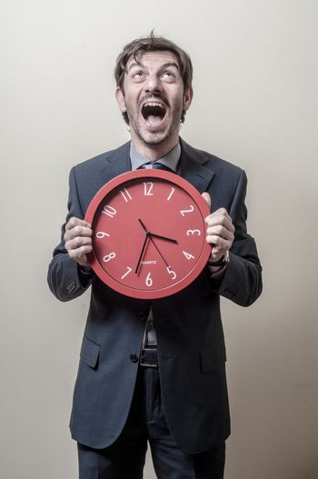 businessman with clock screaming