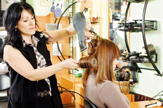 hairdresser drying customer's hair