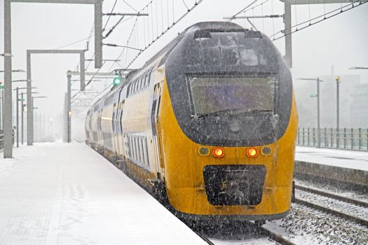 Train in snowstorm departing from Bijlmer station in Amsterdam Netherlands