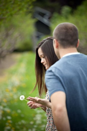 Woman with her boyfriend holding a dandelion outdoors.