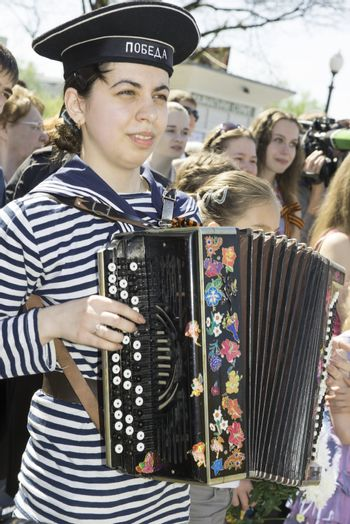 Moscow, Russia - May 9, 2013: Young girl in uniform decorated playing accordion festivities devoted to 68th anniversary of Victory Day.