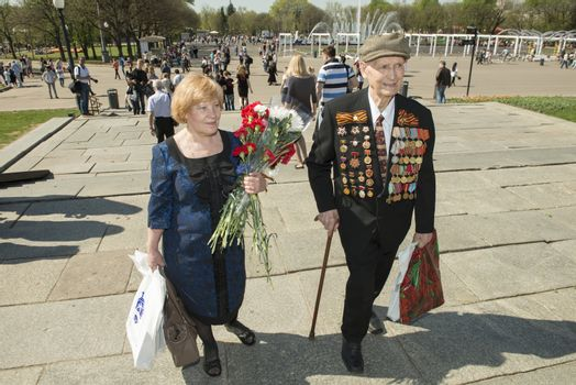 Moscow, Russia - May 9, 2013: Old man veteran of WWII in uniform decorated with numerous orders and medals and his douther bearing bunch of flowers during festivities devoted to 68th anniversary of Victory Day.