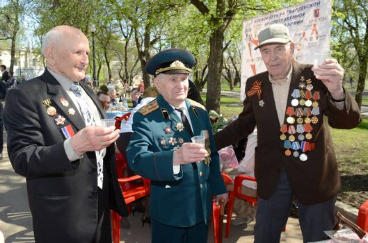 Moscow, Russia - May 9, 2013: Three old man veteran of WWII in uniform decorated with numerous orders and medals   during festivities devoted to 68th anniversary of Victory Day.