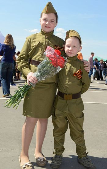 Moscow, Russia - May 9, 2013: Brother and sister in uniform decorated with bearing bunch of flowers during festivities devoted to 68th anniversary of Victory Day.