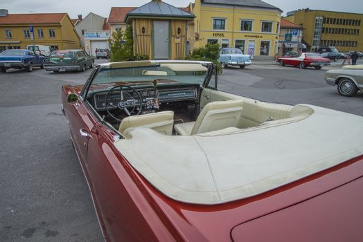 The image is shot at a fish-market in Halden, Norway where there every Wednesday during the summer months are held classic American car show.