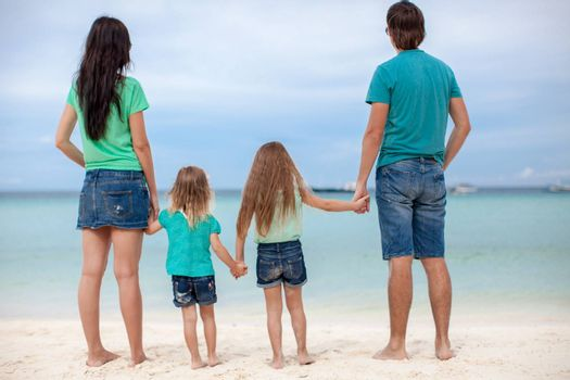 Back view of beautiful family with two kids at exotic beach