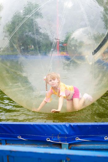 child in the ball in water