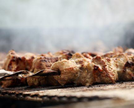 Fresh meat on a steel skewer in a brazier